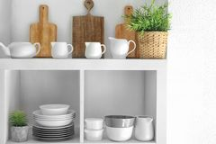 Kitchen shelving with dishes on white background. Kitchen shelving with dishes on white wall background Royalty Free Stock Photo