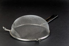 Kitchen sieve on a black background Royalty Free Stock Photo