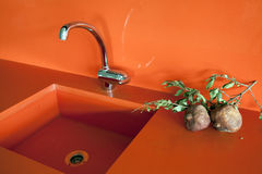 Kitchen sink. Details of modern orange kitchen top. Black wood and orange quartz are the materials used for this contemporary kitchen set Royalty Free Stock Image