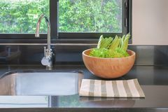 Kitchen sink with a bowl of vegetables in the kitchen royalty free stock photos