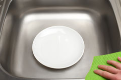 Kitchen sink with clean plate and green rag in hand Stock Photo