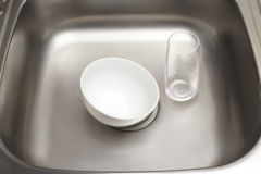 Kitchen sink with clean white bowl and drinking glass. Close up of kitchen sink with clean white bowl and drinking glass stock image