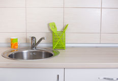 Kitchen sink. Close up of kitchen sink with cup and kitchenware on countertop stock image