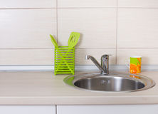 Kitchen sink. Close up of kitchen sink with cup and kitchenware on countertop stock photo