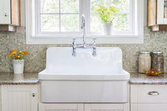 Kitchen sink and counter. Kitchen interior with large rustic white porcelain sink and granite stone countertop under sunny window royalty free stock photography