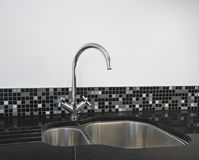 Kitchen sink detail. Detail of a stainless steel kitchen sink on a black granite worktop stock photos