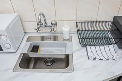 Kitchen sink and faucet. Modern kitchen sink and faucet, plastic sponge drying rack and empty dish drying rack royalty free stock photo