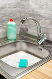 Kitchen sink with foam, cleaning sponge and bottle of detergent Royalty Free Stock Photos