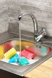 Kitchen sink with foam, running tap water and cleaning sponges stock image