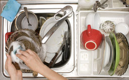 Kitchen sink full with dishes. Hands washing dishes - view from above the kitchen sink Stock Image