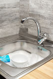 Kitchen sink full of foam, tableware and blue cleaning sponge royalty free stock images