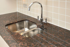 Kitchen Sink with Granite Worktop. Modern 1.5 bowl kitchen sink, with chrome mixer tap, recessed into granite work surface royalty free stock photos