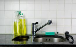 Kitchen sink with metal faucet and yellow dishwashing liquid on a black granite top. Kitchen sink and faucet with a sponge and brush on a black granite table top royalty free stock photography