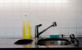 Kitchen sink with metal faucet and yellow dishwashing liquid on a black granite top. Kitchen sink and faucet with a sponge and brush on a black granite table top royalty free stock photo
