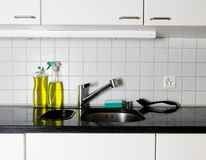Kitchen sink with metal faucet and yellow dishwashing liquid on a black granite top. Kitchen sink and faucet with a sponge and brush on a black granite table top stock photography