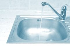 Kitchen sink. Metallic kitchen sink with tap and water stock photos