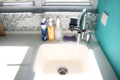 Kitchen sink and running water. Kitchen sink with water running from the faucet Royalty Free Stock Image