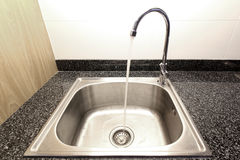 Kitchen sink with running water. From faucet royalty free stock images