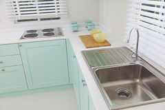 Kitchen sink and stove. Modern kitchen sink and stove, green tone stock photography