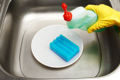 Kitchen sink with water, plate, blue cleaning sponge, detergent. Close up of kitchen sink with water, clean white plate, blue cleaning sponge and bottle of stock photography