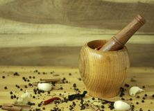 Kitchen spices with mortar on woden surface stock photos