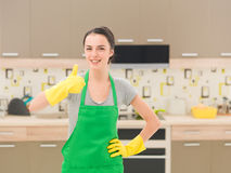 The kitchen is squeaky clean. Cleaning woman happy and excited standing in kitchen, showing thumb up Royalty Free Stock Photography