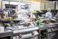 Kitchen staff busy with preparing food in fancy restaurant royalty free stock photos