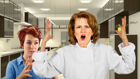 Kitchen Staff. Young waitress and chef fighting in a kitchen Royalty Free Stock Image