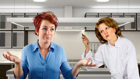 Kitchen Staff. Young waitress and chef fighting in a kitchen Royalty Free Stock Images