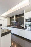 Kitchen with steely canopy. Modern and light kitchen with modern furniture and shining tiles Royalty Free Stock Photography