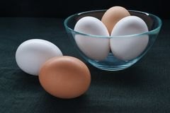 Kitchen still-life. Eggs in a bowl and beside it on a black table-cloth Royalty Free Stock Image