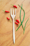 Kitchen still life. Made of wooden fork, five red chili peppers and three stems of green scallion onion lying on wooden table. Copy space Stock Image