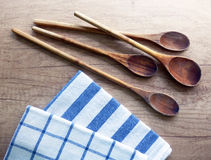 Kitchen still life with cooking spoons and dishcloths on wooden table Stock Photos