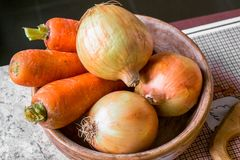 Kitchen still life. Fresh raw carrot and onion in the wooden plate on the table. Close up of a fresh raw vegetables. Different fresh vegetables is an essential Stock Image