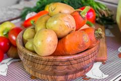 Kitchen still life. Fresh raw carrot and potato in the wooden plate on the table. Close up of a fresh raw vegetables. Different fresh vegetables is an essential Stock Photo