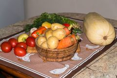 Kitchen still life. Fresh raw carrot and potato in the wooden plate on the table. Close up of a fresh raw vegetables. Different fresh vegetables is an essential Royalty Free Stock Photos