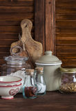 Kitchen still life. Olive chopping board, glass jar with flour, vintage utensils - bowl, Cup, pot and jars of spices and homemade Stock Photography