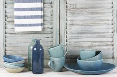 Kitchen still life. Simple rustic kitchen still life: handmade blue ceramic dish, bowls, mugs, glass bottles and towel against shabby wooden shutters stock photography
