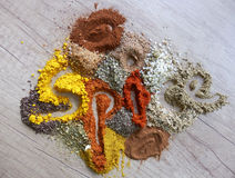 Kitchen still life with spice word. Color detail photography of the spice word made of different herbs and spices on wooden table from the top view royalty free stock photo