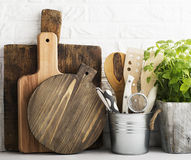 Kitchen still life on a white brick wall background: various cutting boards, tools, greens for cooking, fresh vegetables Stock Image