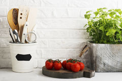 Kitchen still life on a white brick wall background: various cutting boards, tools, greens for cooking, fresh vegetables. Selective focus Royalty Free Stock Photos