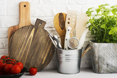 Kitchen still life on a white brick wall background: various cutting boards, tools, greens for cooking, fresh vegetables Royalty Free Stock Images
