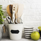 Kitchen still life on a white brick wall background: various cutting boards, tools, greens for cooking, fresh vegetables Stock Photo