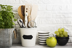 Kitchen still life on a white brick wall background: various cutting boards, tools, greens for cooking, fresh vegetables Stock Photography