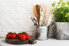 Kitchen still life on a white brick wall background: various cutting boards, tools, greens for cooking, fresh vegetables. Selective focus Royalty Free Stock Image