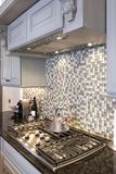 Kitchen stove and backsplash. Beautiful kitchen stove and backsplash made from glass tile stock images