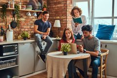 Kitchen in student dormitory. Group of interracial students engaged in education. royalty free stock images