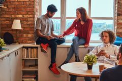 Group of interracial students resting in student dormitory. royalty free stock images