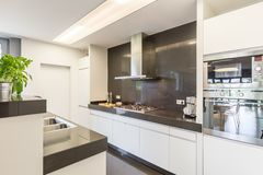 Kitchen with stylish amenities. Modern kitchen interior with two worktops, kitchen amenities and white furnitures royalty free stock photo
