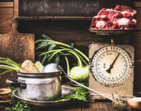 Kitchen table with cooking pot, ladle, vegetables and old weigher with raw meat , preparation of soup , broth or stew, front view. Country style stock image